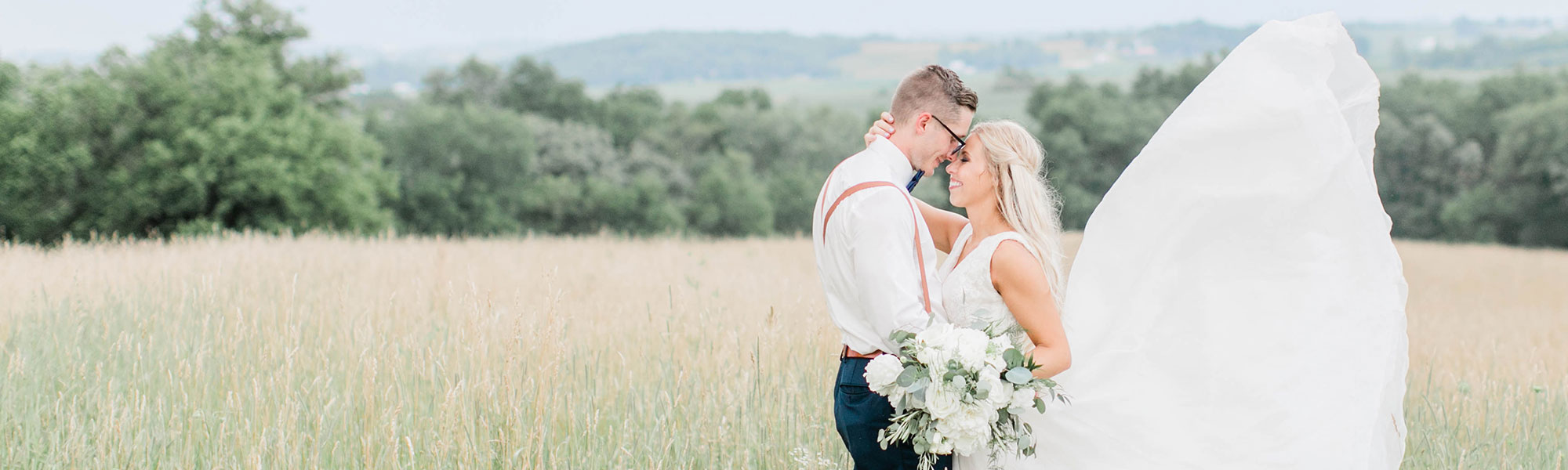 wedding couple in the field of tall grass at Red Acre Barn