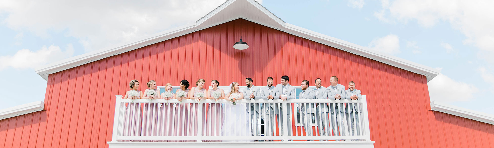 wedding party on the balcony of the barn